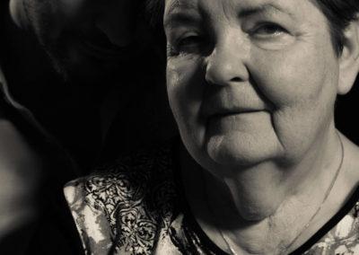 Schwarzweiß-Portrait einer Mutter und deren erwachsenen Sohn. Mutter im Vordergrund Sohn lehnt Kopf im Hintergrund an ihren.