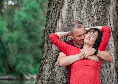 Portrait eines Ehepaars vor einem dicken Baumstamm. Frau steht vor Mann, beide haben die Arme umeinander geschlungen. Im Hintergrund ein See und weitere Bäume.