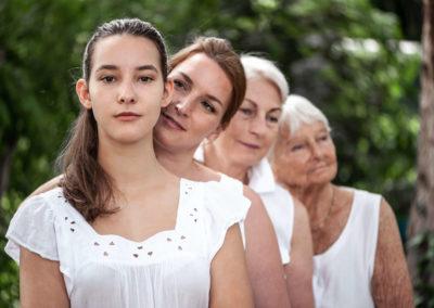 Portrait von einer Familie. Vier Frauen verschiedener Generationen in weißer Kleidung. DStehen Hintereinander nach dem alter geordnet. Im Hintergrund Bäume.