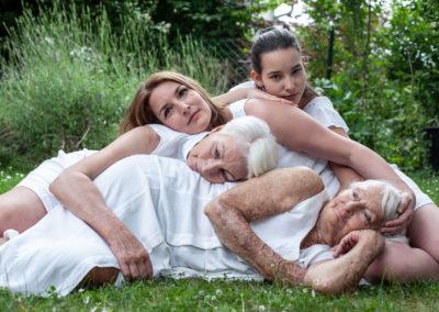 Portrait von einer Familie. Vier Frauen verschiedener Generationen in weißer Kleidung. Liegen in der Wiese. Im Hintergrund. Sträucher, Bäume und andere Pflanzen.