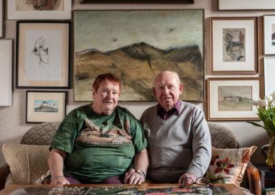 Portrait eines älteren Ehepaares auf ihrem Sofa. Im Hintergrund eine Wand voller Kunstwerke.