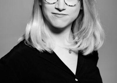 Schwarzweiß-Portrait einer jungen Frau mit Brille und halblangen blonden Haaren.