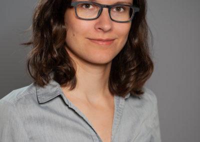 Portrait einer jungen Frau mit Brille und halblangen braunen Haaren.