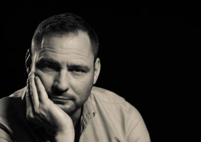 Portrait eines attraktiven Mannes, der nachdenklich das Kinn auf eine Hand gestützt hält. Hintergrund und Umgebung sind dunkel.