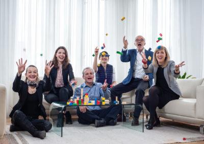 Team-Portrait in Aktion: 6 Unternehmensberater*innen werfen mit bunten Holzklötzchen Richtung Kamera.