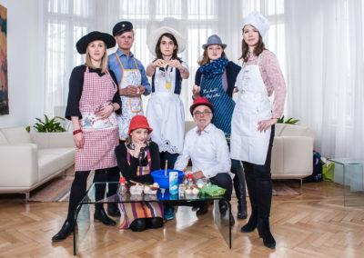 Team-Portrait in Aktion: 6 Unternehmensberater*innen als Köche verkleidet posen mit einem aufgeschlagenen, fallenden Ei.