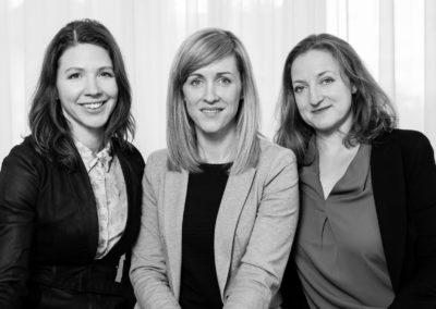 Schwarzweiß-Portrait dreier Frauen nebeneinander, alle in die Kamera schauend.