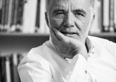 Schwarzweiß-Portrait eines älteren Mannes sitzend, den Kopf in die Hand gestützt. Im Hintergrund Bücherschränke.