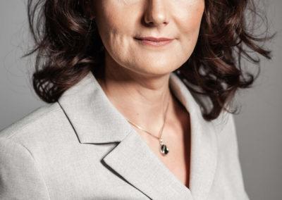 Portrait einer brünetten Frau mit schulterlangen Locken und grau-beigen Anzug.