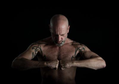 Portrait eines tätowierten Mannes. Oben ohne. Hält geballte Fäuste vor der Brust zusammen.