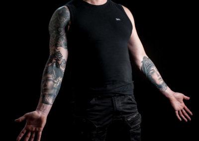 Portrait eines tätowierten Mannes mit nach unten ausgestreckten offenen Händen.