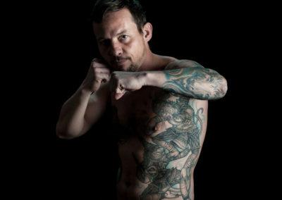 Portrait eines tätowierten Mannes, oben ohne in Kampfposition.