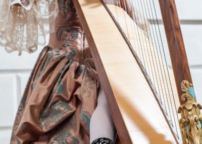 Portrait einer Frau im Ballkleid mit Harfe. Im Hintergrund umrisse einer weißen Wand mit schnörkel