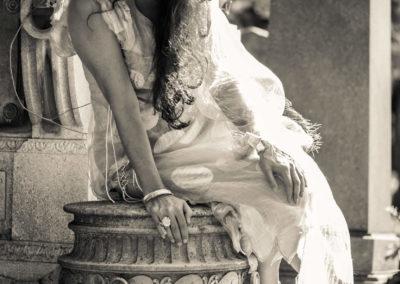 Schwarzweiß-Portrait einer Frau als Braut hergerichtet auf steinerner Vasenskulptur sitzend. Im Hintergrund größere Skulptur, Obelisk und Nadelbäume.