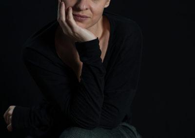 Portrait einer kurzhaarigen, blonden Frau, sitzend und schwarz gekleidet.