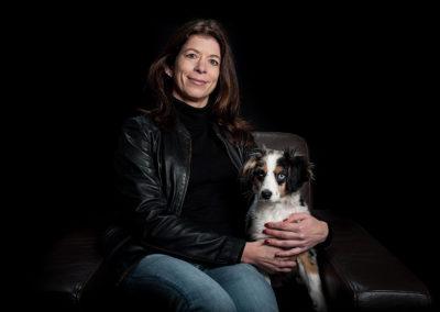 Portrait einer auf einem Sofasessel sitzenden Frau. Neben ihr ein junger weißer Hund mit schwarzen und braunen Flecken.