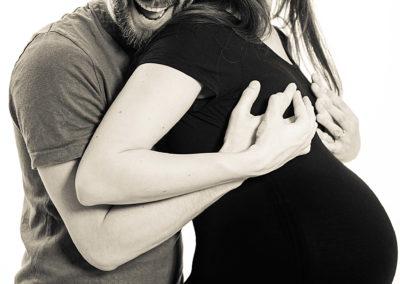 Schwarzweiß-Portrait eines Ehepaars. Frau ist schwanger. Mann umarmt sie von hinten und schaut, verrückt lachend in die Kamera.