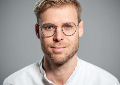 Portrait eines dunkelblonden Mannes mit Brille und Dreitagesbart