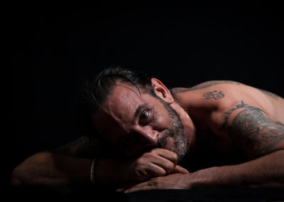Portrait eines tätowierten, am Bauch liegenden Mannes mit nacktem Oberkörper