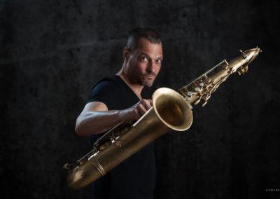 Portrait eines jüngeren Saxofonspielers der das Saxofon in die Kamera hält.
