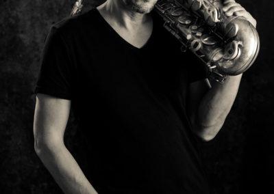 Schwarzweiß-Portrait eines jüngeren Saxofonspielers.