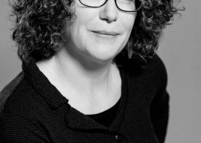 Schwarzweiß-Portrait einer jungen Frau mit Brille und gelockte, schulterlangen Haaren.
