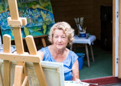 Portait einer älteren Malerin beim Arbeiten auf der Staffelei. Im Hintergrund anderes Gemälde auf Staffelei und einige Pinsel.