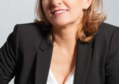 Studioportrait einer blonden Frau im Anzug.
