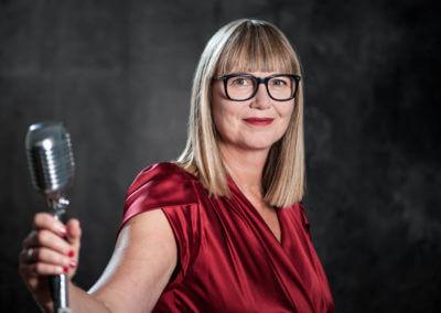 Portrait einer blonden Frau mit Brille und rotem Kleid. Hält Standmikrofon in Hand mit rot lackierten Nägeln.