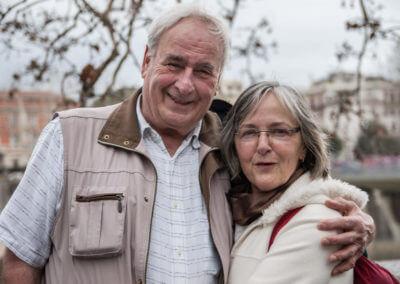 Portrait eines älteren Ehepaars. Stehen nebeneinander. Mann fasst Arm über die Schulter der Frau. Im Hintergund Herbstliche Äste und Gebäudeumrisse.