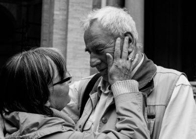 Schwarzweiß- Portrait eines älteren Ehepaars. Schauen sich tief in die Augen. Frau hält Wange von Mann. Im Hintergund der Teil eines Gebäude.