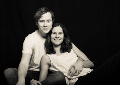 Schwarzweiß-Portrait eines jungen Liebespaar. Mann im Schneidersitz, Frau lehnt liegend an ihm. Hintergrund schwarz.