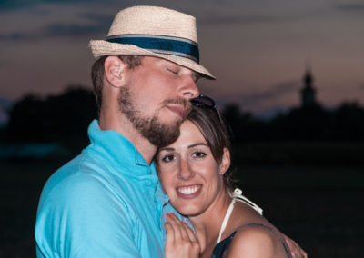 Portrait eines jungen Paares in der Abenddämmerung. Im Hintergrund die Silhouetten einer Dorfkirche.