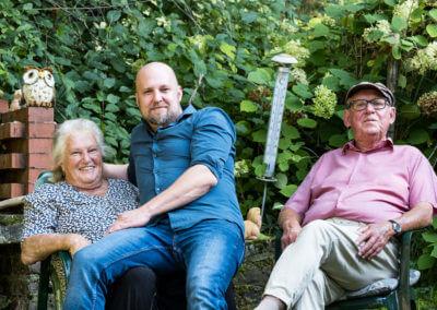 Portrait einer dreiköpfigen Familie. Sohn erwachsen, sitzt auf Mutters Schoß auf einem Gartenstuhl. Hintergrund Sträucher.