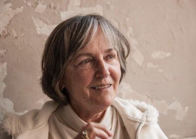 Portrait einer älteren Frau mit kinnlangen grauen Haaren vor einer crémefarbenen bröckelnden Wand.