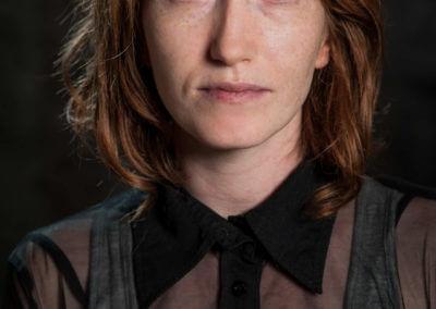 Portrait einer rothaarigen Frau mit halblangen Haaren und ernstem Blick..