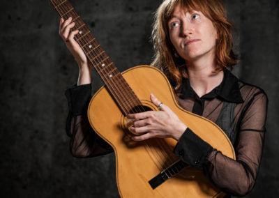 Portrait einer sitzenden Frau mit Gitarre und halblangen roten Haaren. Dramatische Bardengeste.