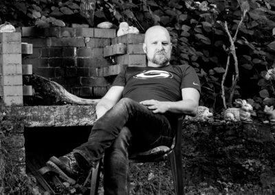 Schwarzweiß- Portrait von einem glatzköpfigen Mann im Gartenstuhl. Im Hintergrund Holzofengrill und Sträucher.