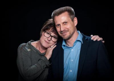 Studioportrait eines Ehepaares, inniglich aneinander geschmiegt. Hintergrund schwarz.