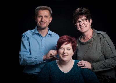 Studioportrait von Mutter, Vater und Tochter, erwachsen. Necken sich gegenseitig.